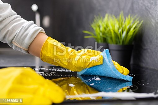 The girl washes the stove with a blue sponge in yellow gloves