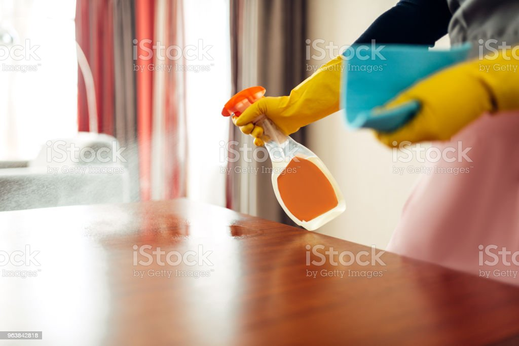 Housemaid hands cleans table with cleaning spray - Royalty-free Adult Stock Photo