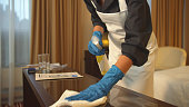 Housemaid in uniform and gloves wipe the table with rag in hotel room