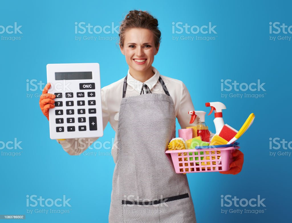 Hausmädchen mit einem Korb mit Reinigungsmittel und Bürsten zeigen große Rechner – Foto