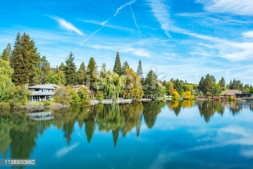 Stock photograph of waterfront houses along Mirror Pond on the Deschutes River in downtown Bend Oregon USA on a sunny day.