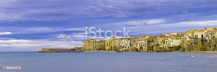 istock Houses along the shoreline and cathedral in background Cefalu Sicily. Italy. 1133642273