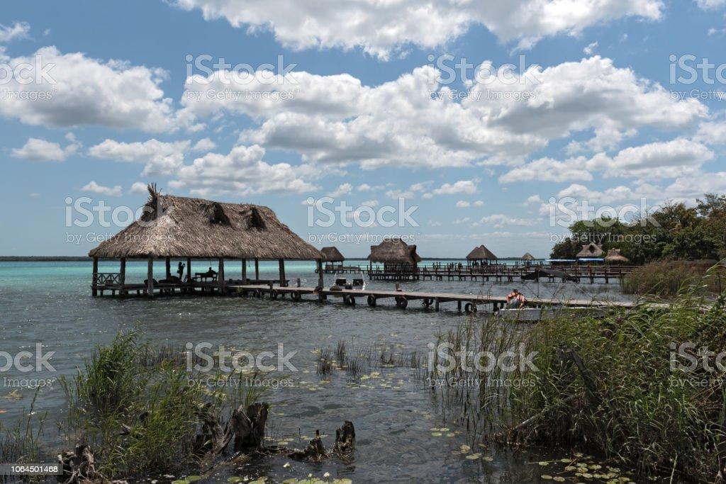 casas y muelle en la orilla de la laguna de bacalar, quintana roo, México - foto de stock