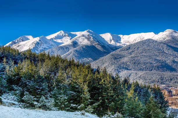 Houses and snow mountains in Bansko, Bulgaria stock photo
