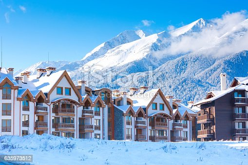 Wooden chalet, houses and snow mountains landscape panorama in bulgarian ski resort Bansko, Bulgaria