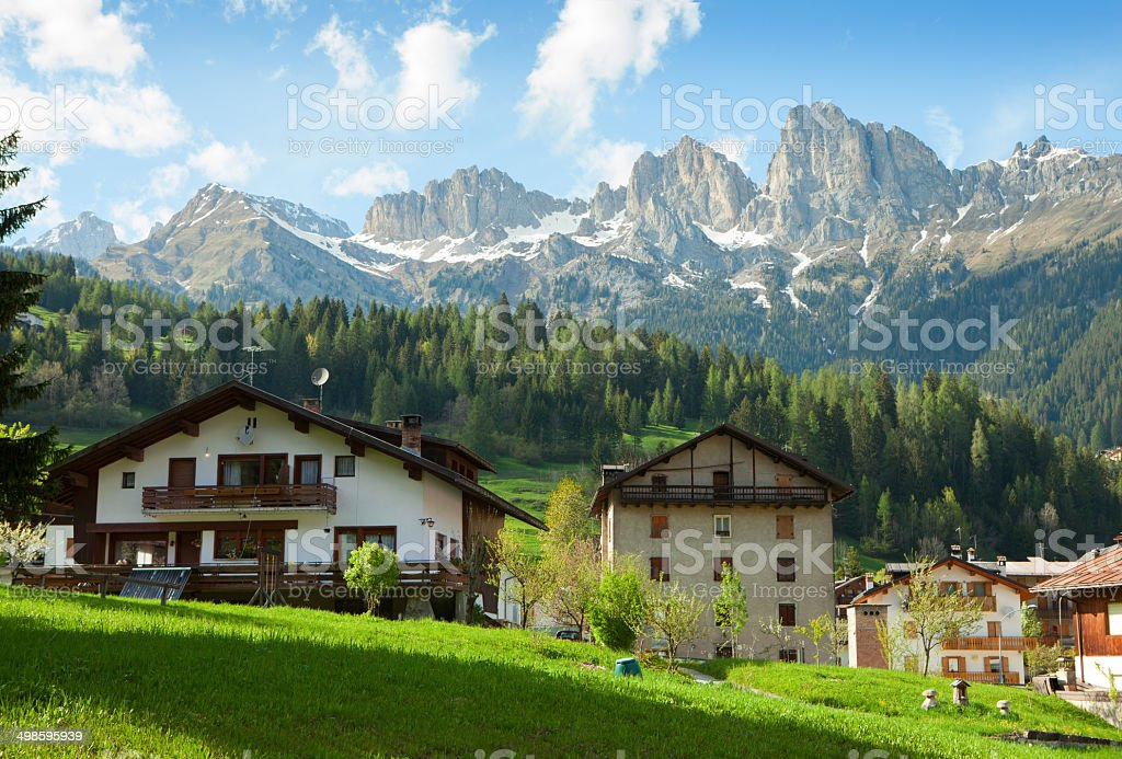 Houses are surrounded by the Dolomites, royalty-free stock photo