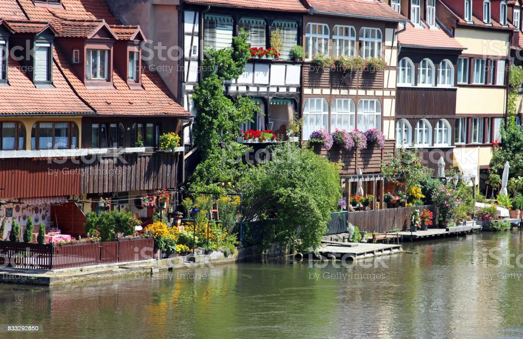 houses at a river with little green gardens stock photo
