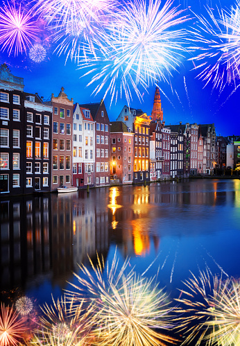 Houses over canal with mirror reflections at night with fireworks, Amstardam, Netherlands