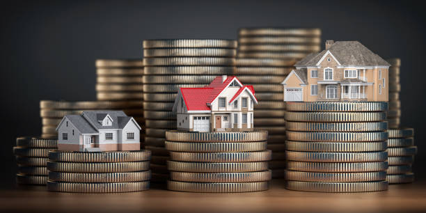 houses of different size with different value on stacks of coins. concept of  property, mortgage and real estate investment. - vendere foto e immagini stock