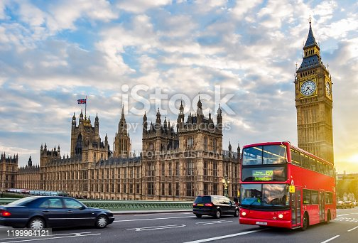 London, UK - April 2017: Houses of Parliament with Big Ben and double-decker bus on Westminster bridge at sunset