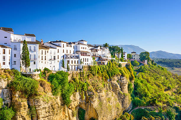 Houses on a cliff in Ronda, Spain surrounded by green trees stock photo