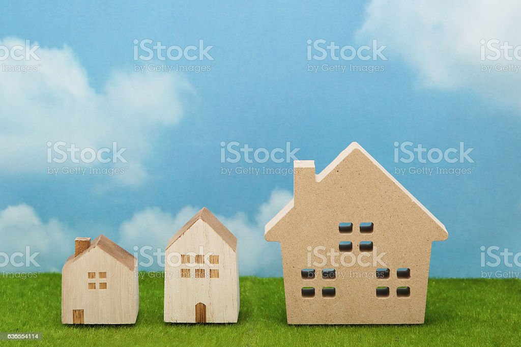 Houses on green grass over blue sky and clouds. stock photo