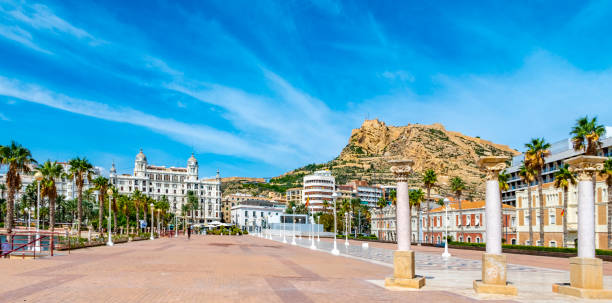 Houses on the promenade of Alicante, Spain in the Baroque style among palm trees, Pinnacles and spiers stock photo