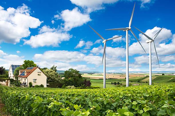 häuser mit solarzellen auf dem dach und windturbinen - französische häuser stock-fotos und bilder