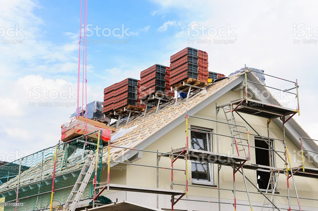 Housetop of new building will be roofed stock photo