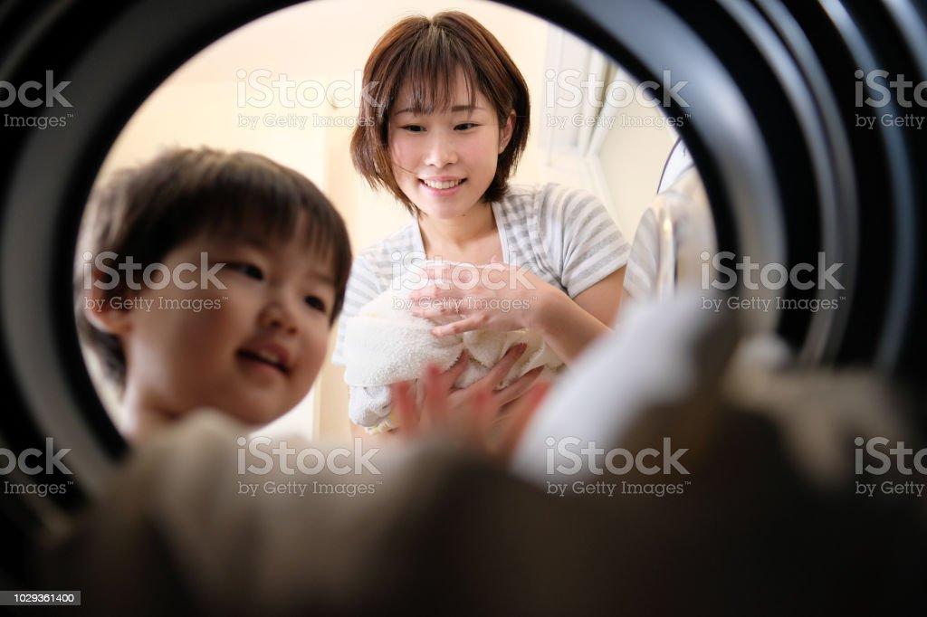 主婦と洗濯機から洗濯物を取り出して彼女の子供 ストックフォト