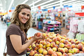 Caucasian Housewife buying peaches in a megastore