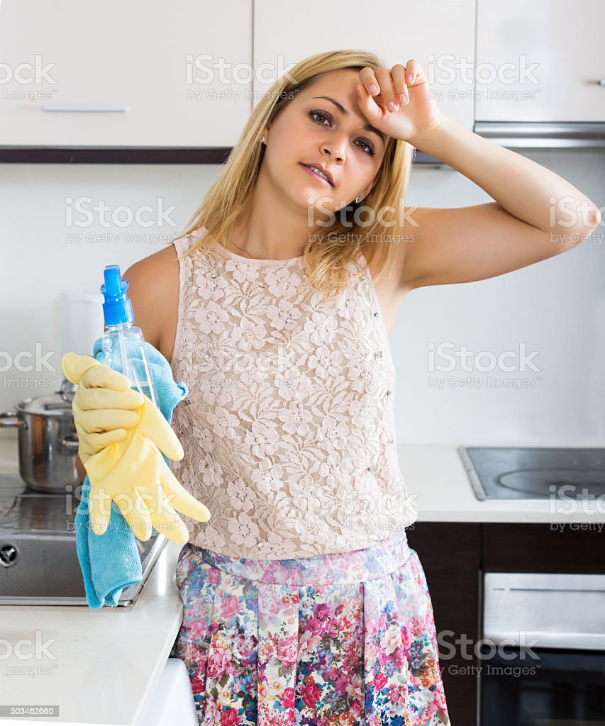 Housewife cleaning furniture in kitchen stock photo