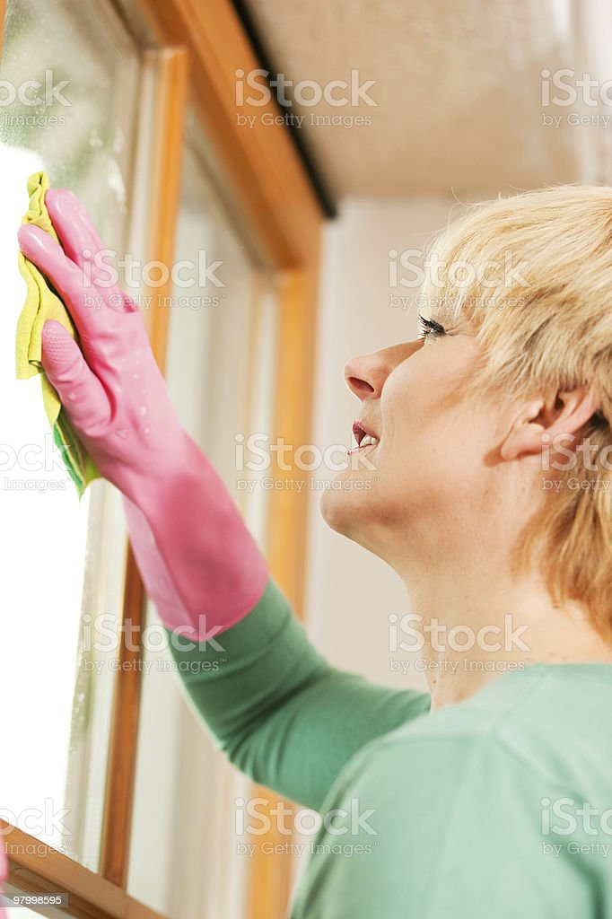 housewife cleaning her windows in rubber gloves royalty-free stock photo