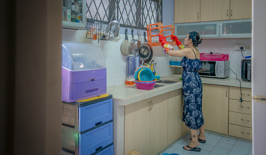 Sideview of Asian housewife cleaning kitchen items in the kitchen.
