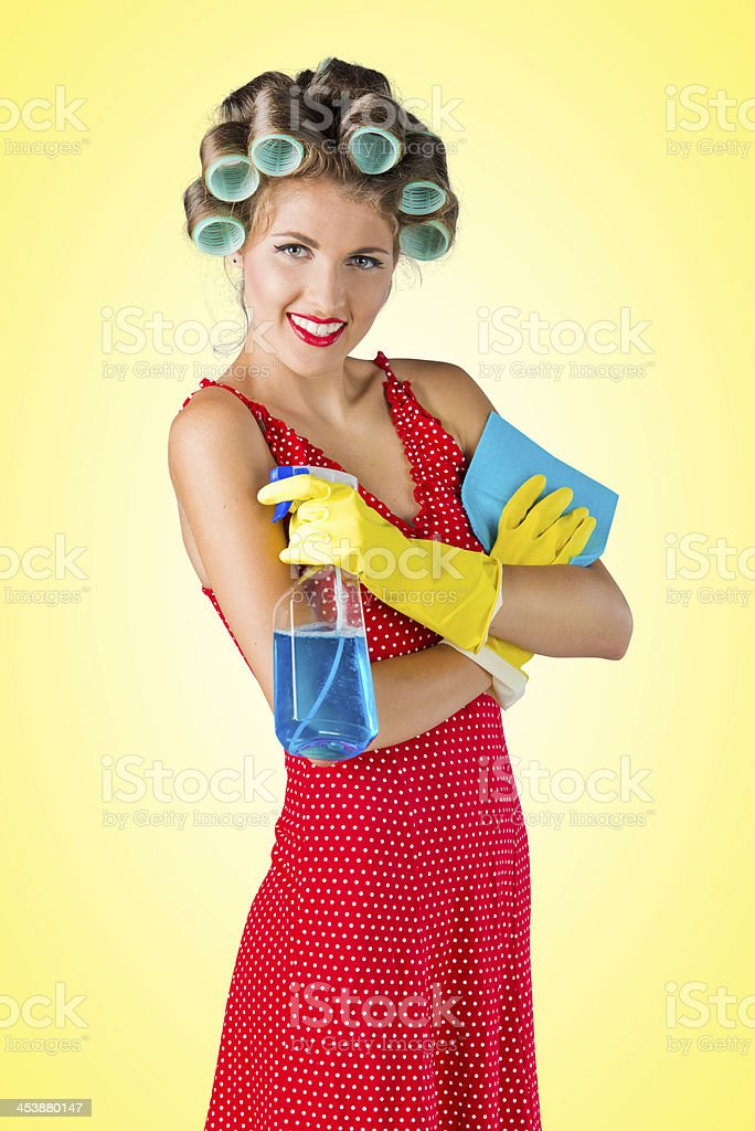 Housewife cleaning with spray, yellow background stock photo