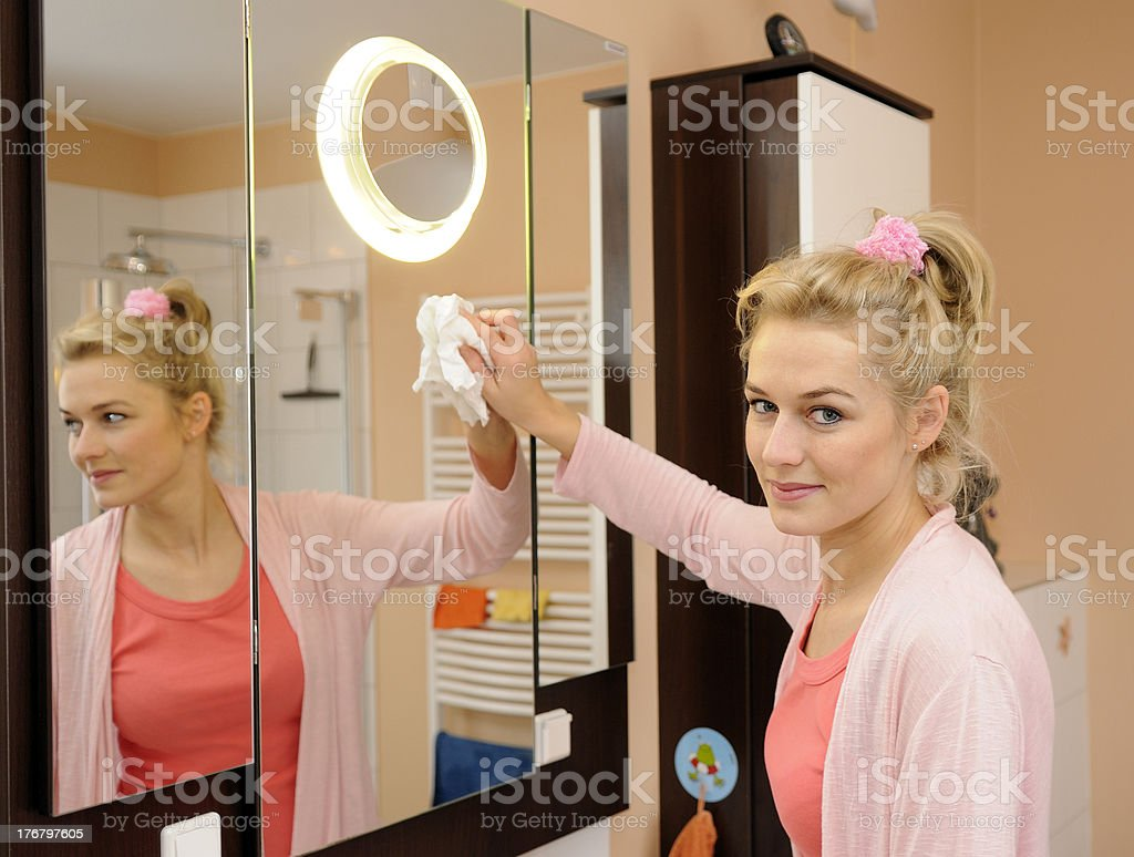 housewife cleans a mirror stock photo