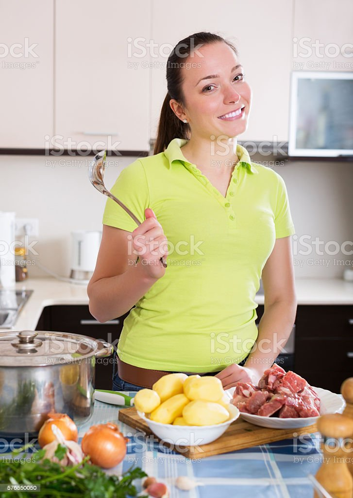 Housewife cooking soup with meat stock photo