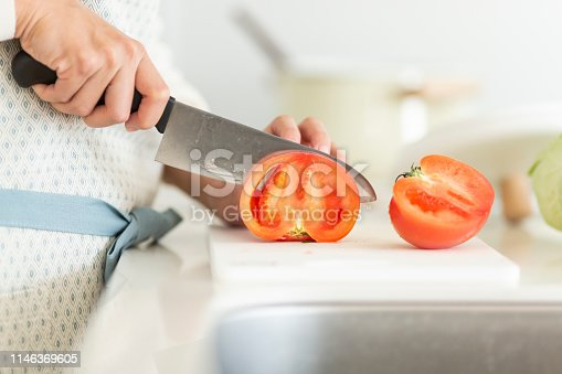 619063596 istock photo Housewife cutting a tomato with a kitchen knife 1146369605