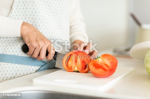 619063596 istock photo Housewife cutting a tomato with a kitchen knife 1146369608