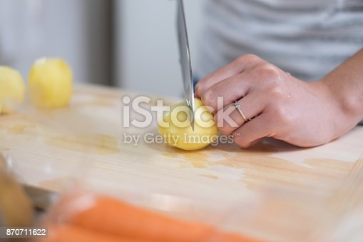 619063596 istock photo housewife cutting potatoes in kitchen 870711622