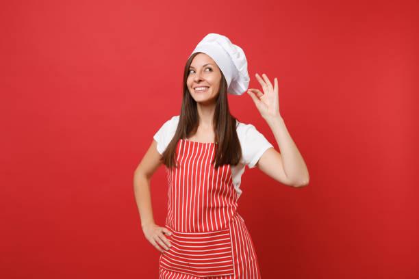 Ama de casa mujer chef cocinero o panadero en delantal rayas blancas t-shirt, sombrero de chef toque aislado sobre fondo de pared roja. Sonriente mujer lindo tranquilo haciendo bien gusto placer signo. Se burlan de concepto de espacio de copia. - foto de stock
