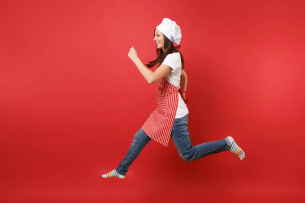 Ama de casa mujer chef cocinero o panadero en delantal rayas blancas t-shirt, sombrero de chef toque aislado sobre fondo de pared roja. Longitud total retrato ama de casa mujer salto alto. Se burlan de concepto de espacio de copia. - foto de stock