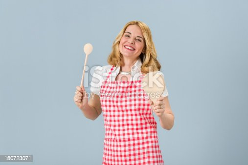 istock Housewife holding mixing spoon and cutting board 180723071