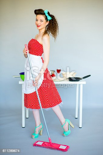 Pinup housewife in the kitchen trying to clean up