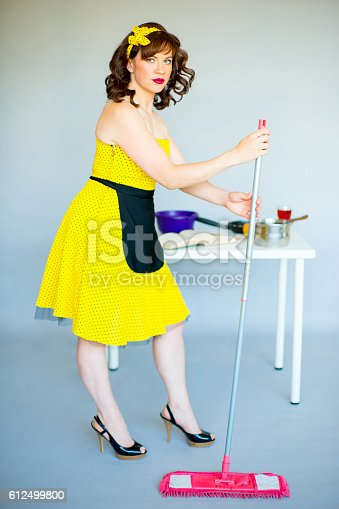 Pinup housewife in the kitchen trying to cook something