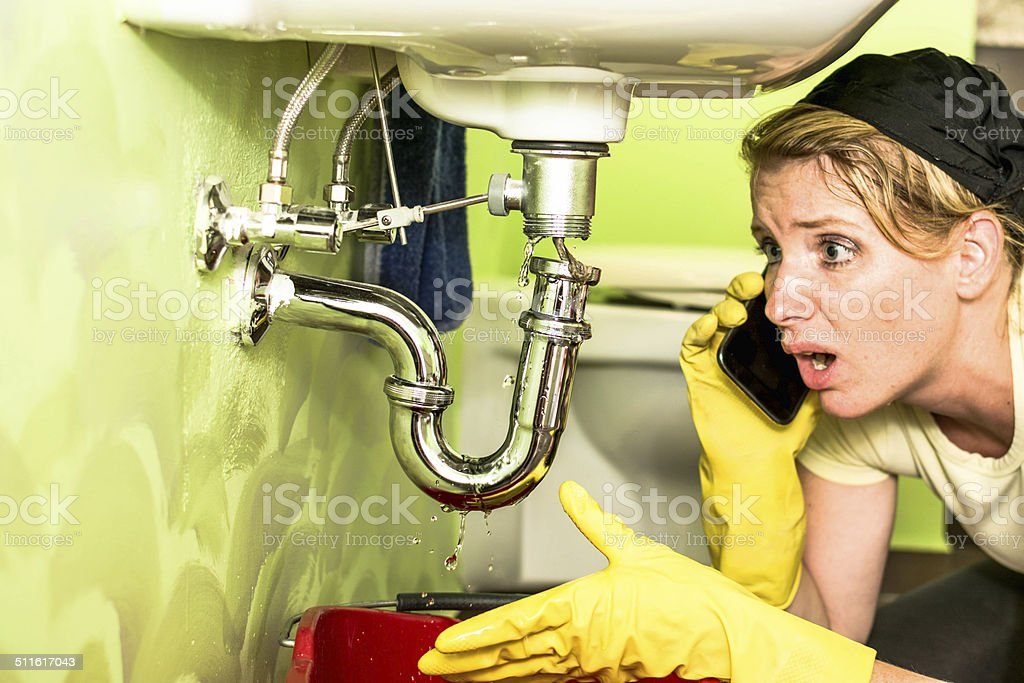 Housewife looking a siphon under the sink stock photo