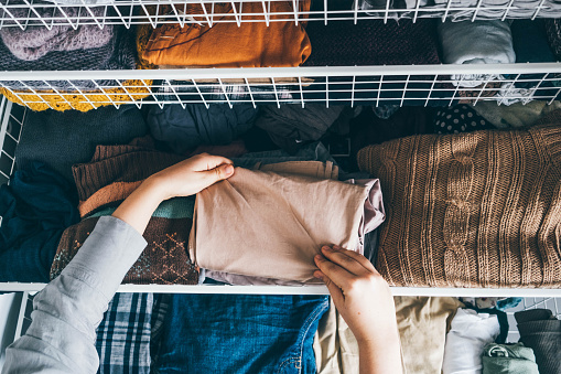 Housewife organizing clothes in wardrobe. Woman sorting out wardrobe.