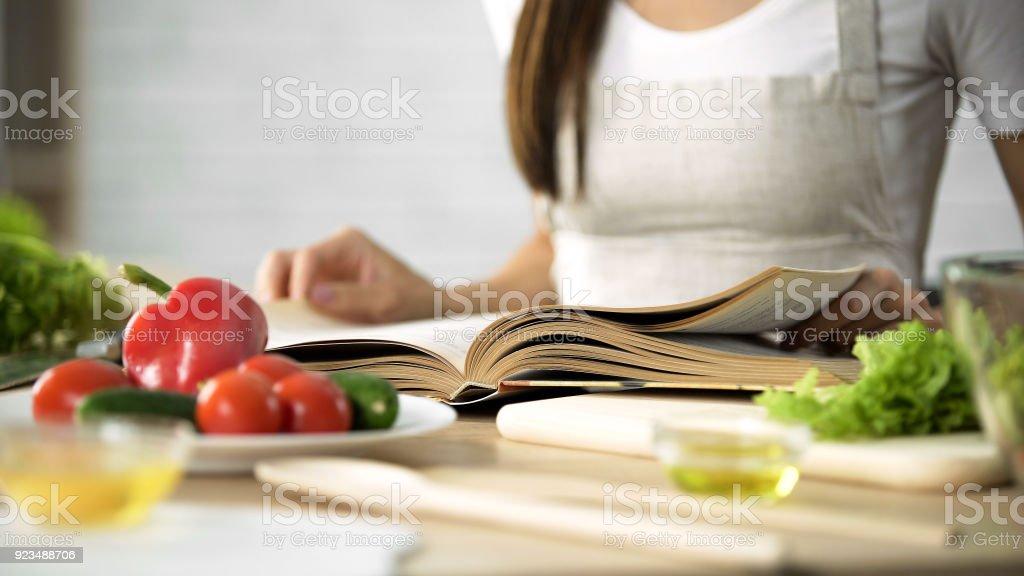 Hausfrau Kochbuch mit frischem Gemüse und Küchengeräte auf Tabelle lesen – Foto