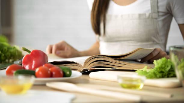 dona de casa, lendo livro de culinária com legumes frescos e utensílios de cozinha na tabela - receita - fotografias e filmes do acervo