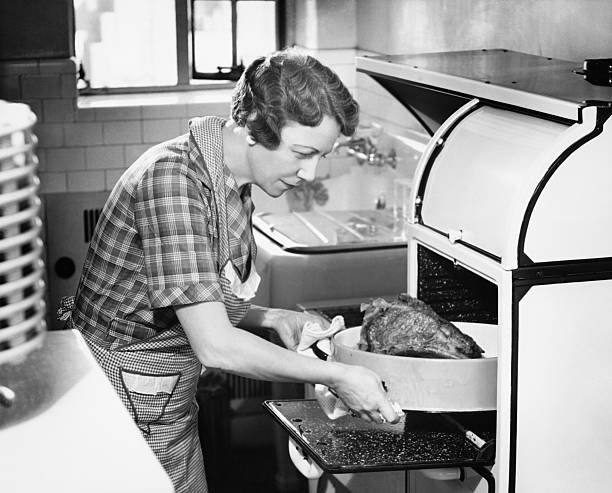 Housewife removing turkey from oven, (B&W)  cooking black and white stock pictures, royalty-free photos & images
