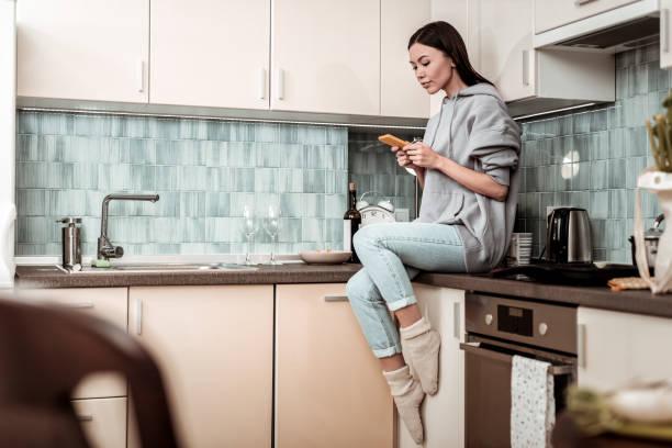 ama de casa sentado junto a la cocina y el mensaje de la lectura en el teléfono - social media fotografías e imágenes de stock