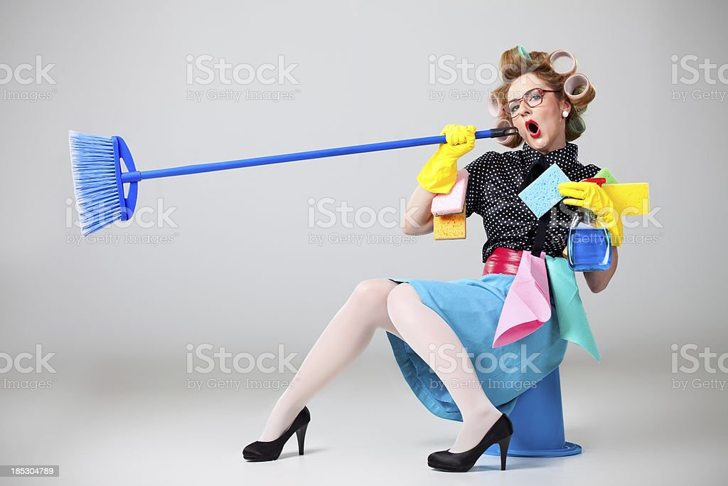 Housewife sitting on bucket and singing into broom stock photo