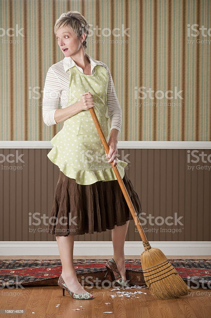 Housewife Sweeping Dirt Under The Rug royalty-free stock photo
