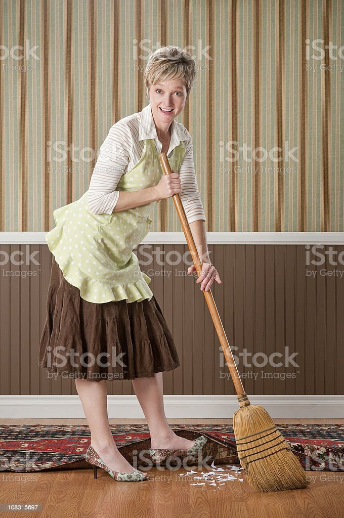 Housewife Sweeping Dirt Under The Rug stock photo