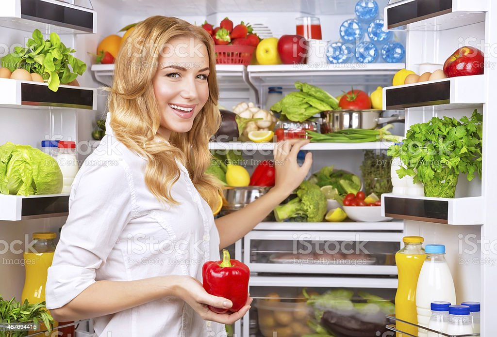 Housewife take red pepper from fridge stock photo