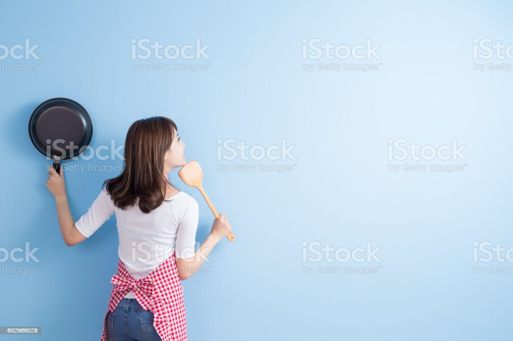 housewife take wok and spoon stock photo