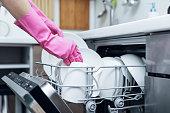 主婦の台所食器洗い機自宅からきれいな食器を取り出す