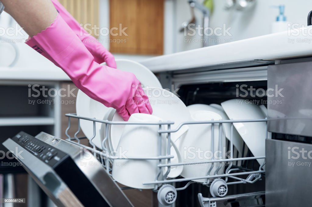 housewife taking out clean dishware from dishwasher at home kitchen stock photo