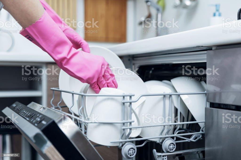 Hausfrau, die Entnahme von sauberem Geschirr aus Geschirrspüler zu Hause Küche – Foto