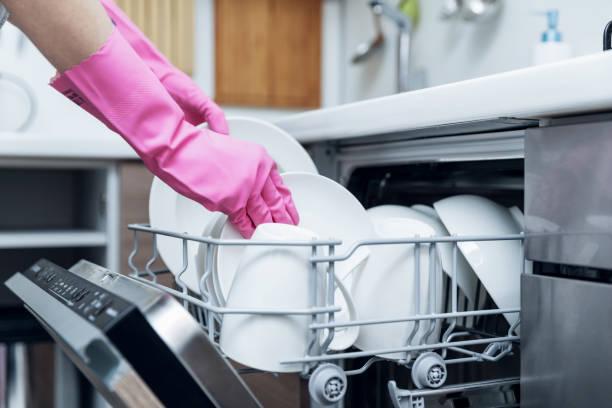 huisvrouw nemend schone serviesgoed uit de vaatwasser thuis keuken foto